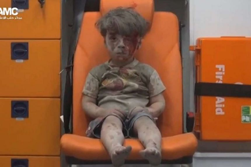 A still image from a video posted on social media said to be shot in Aleppo on Aug 17, 2016, shows a boy with bloodied face sitting in an ambulance, after an airstrike.