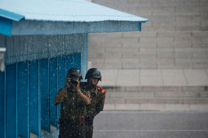 North Korean soldiers keep watch toward the South side as it rains at the truce village of Panmunjom, along the Demilitarized Zone (DMZ) on July 27.
