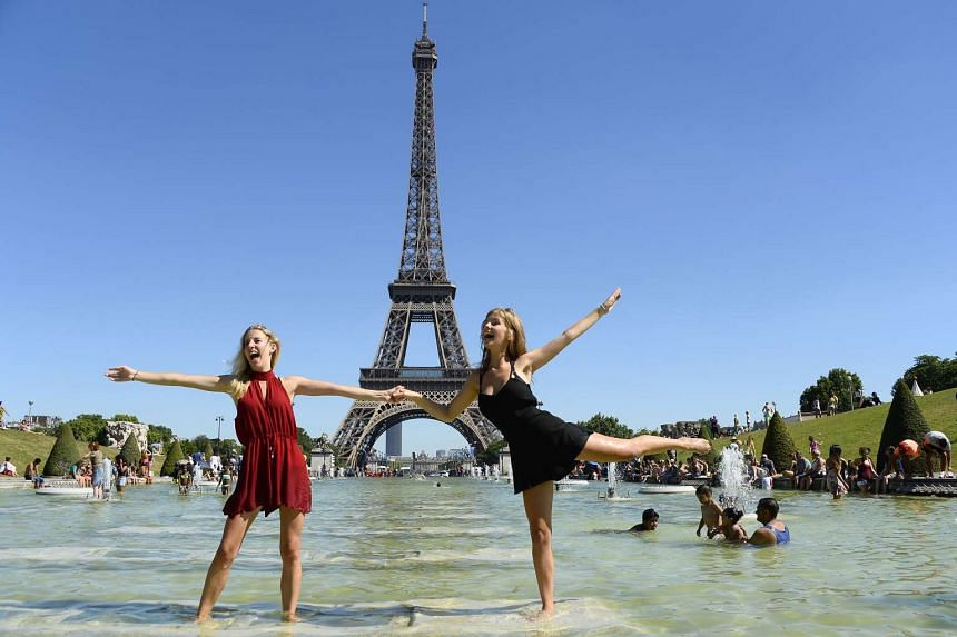 Two young women cool off at the Trocadero fountain in front of the Eiffel Tower in Paris on July 19, 2016.