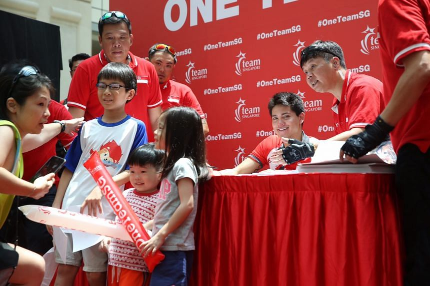Joseph Schooling signing autographs and gamely posing for photographs at Raffles City.