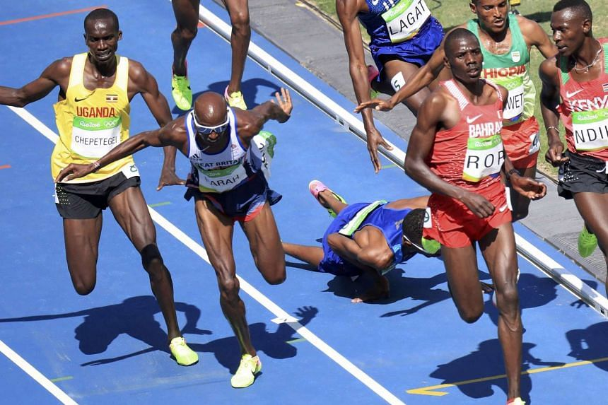 British runner Mo Farah (second from left) stumbles as he collides with Mead Hassan of USA who falls.