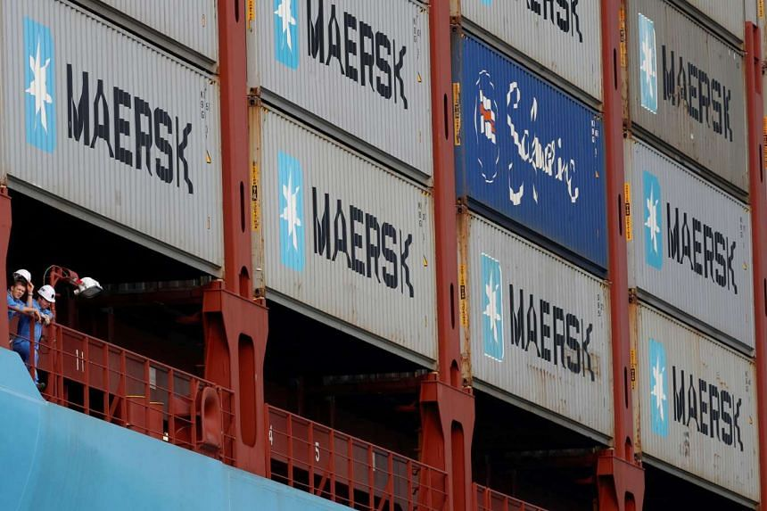 Crew members look out from the container ship, the MV Maersk Mc-Kinney Moller, as it berths during its maiden port of call at a PSA International port terminal in Singapore in 2013.