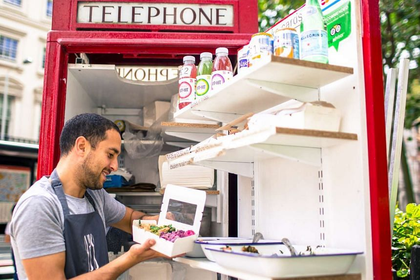 Ben Spier, owner of Spier Salads, fulfills a customer order at his converted red telephone box in Bloomsbury Square, in London.