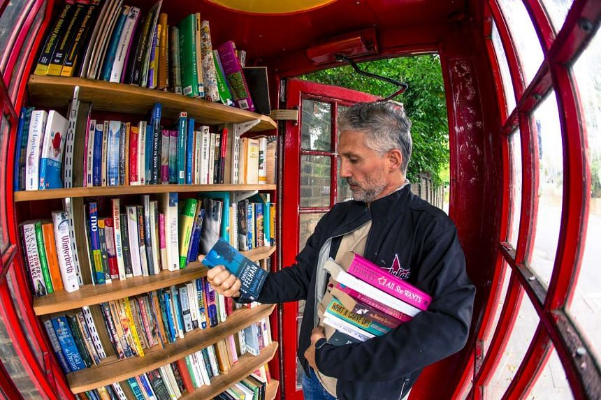 A visitor picks up books from an honor library located inside a converted red telephone box, on Lewisham Way, in London.