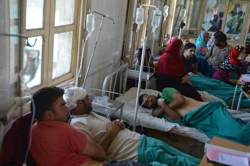Injured Kashmiri patients, who were allegedly beaten up by Indian army soldiers, are comforted by relatives while lying on hospital beds in Srinagar on Aug 18.