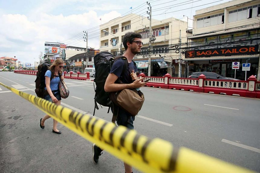 Foreign tourists walk past police line at the bomb blast site in Hua Hin resort city, Thailand on Aug 12, 2016.