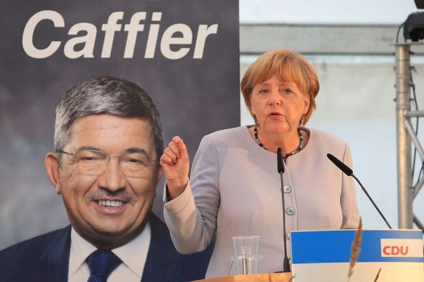 Angela Merkel speaks next to a poster of Lorenz Caffier, chairman of the Christian Democratic Union (CDU) during a campaign event in Boldekow, Germany, on Aug 18.
