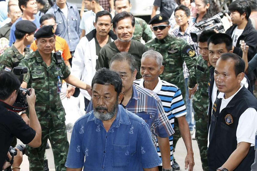 Some of the fifteen Thais suspected of being against the military junta government, are escorted by the military and police officers at the Crime Suppression Division, in Bangkok, Thailand on Aug 19.