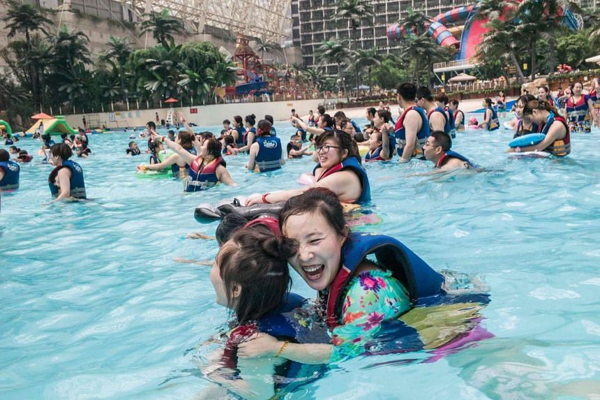 People in life jackets enjoying the waves at the water park in the New Century Global Centre.