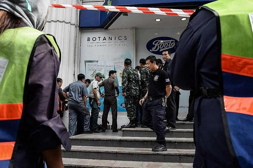 Bystanders watch as police dispose of a suspicious-looking bag in the Ratchaprasong district in Bangkok yesterday. The area is popular with tourists. The incident turned out to be a bomb scare.