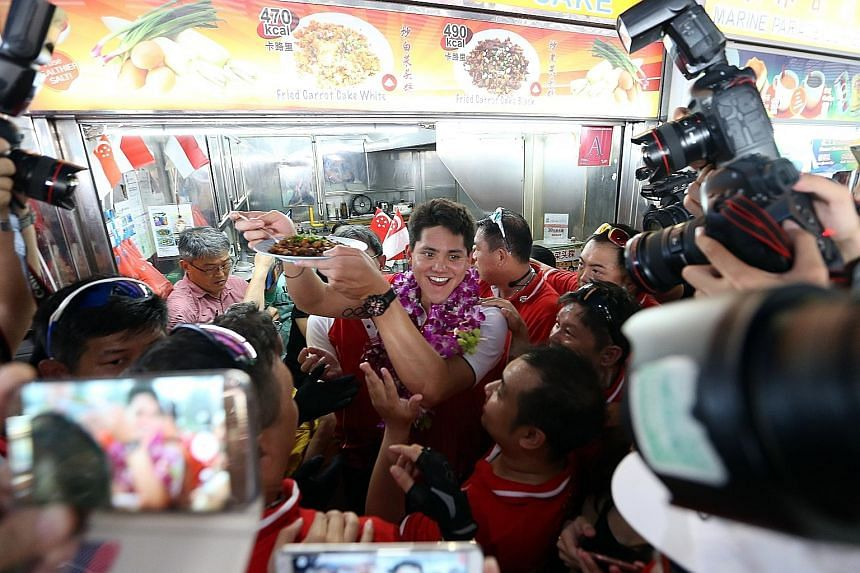 Schooling with a plate of his favourite black chye tow kueh from Bee Bee Carrot Cake at Marine Terrace Market, his first pit stop during his victory parade yesterday. Cheering fans not only packed the pit stops, but lined the bus route to show their
