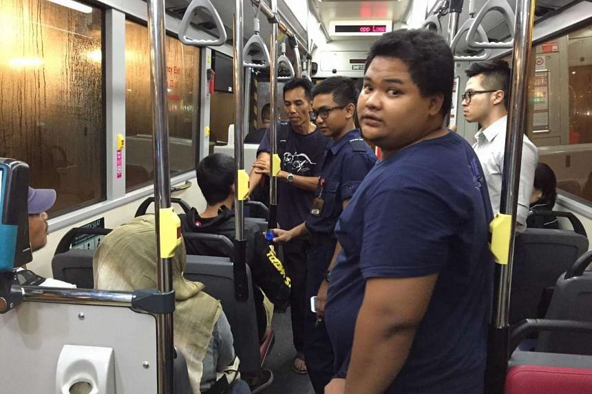 Full-time national servicemen Md Hafiz (in uniform) and Hendriyanto (facing camera) helping a bus passenger who suffered an asthma attack on Aug 17, 2016.