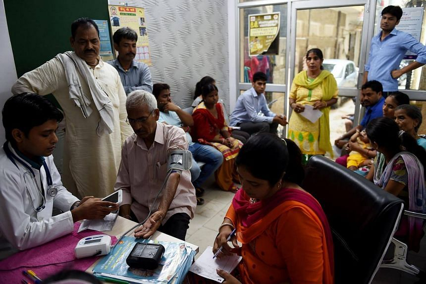 Indian Doctor Shoebul Haque (left) checks a patient as others wait at a Mohalla clinic (neighbourhood clinic) in New Delhi.