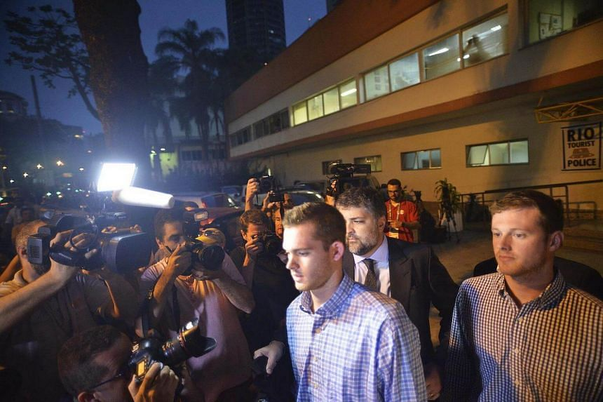 US swimmers Gunnar Bentz (centre) and Jack Conger (right) after being questioned by the Special Police Station of Tourists Attention in Rio de Janeiro, Brazil on August 18.