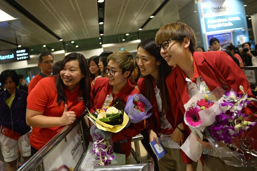 (From right) Singapore paddlers Zhou Yihan, Yu Mengyu and Feng Tianwei posing for a picture with a fan after they returned to Singapore, at Changi Airport on Aug 19, 2016.
