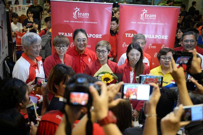 National paddlers Zhou Yihan (second from left), Feng Tianwei (centre) and Yu Mengyu (second from right) greeting cheering fans at Changi Airport on Aug 19, 2016.