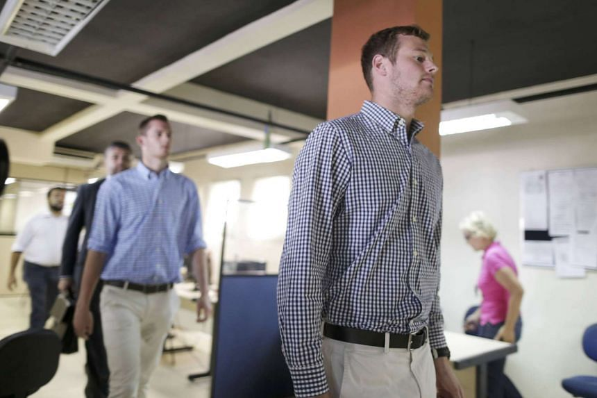 US swimmers Jack Conger and Gunnar Bentz are escorted into a police station the morning after they were stopped from boarding a flight to the US.