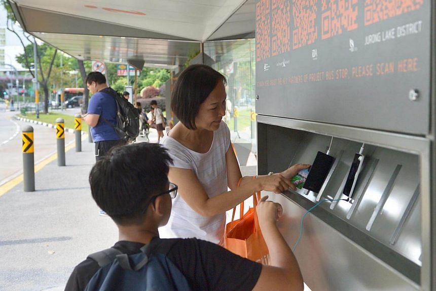 Teoh Wen Da, 14, from Bukit Batok Secondary School teaching a commuter how to use the charging station.