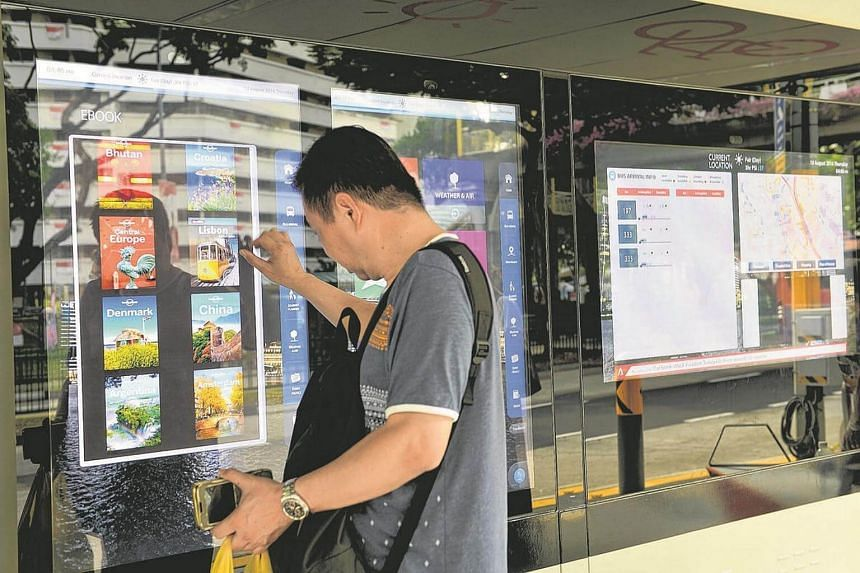 A commuter looking through the interactive screens at the bus stop.