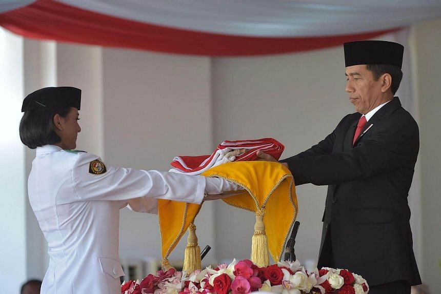 Indonesian President Joko Widodo (right) gives a national flag to Indonesian student Nilam Sukmapawening during the Indonesian Independence day ceremony in Jakarta.