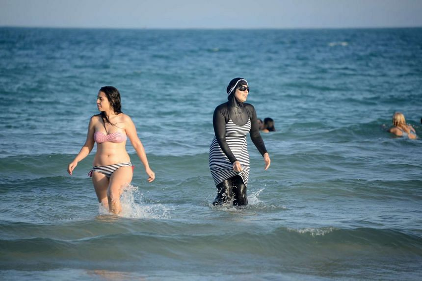 Tunisian women, one (right) wearing a burkini, walk in the sea at Ghar El Melh beach near Bizerte, north-east of the capital Tunis, on Aug 16, 2016.