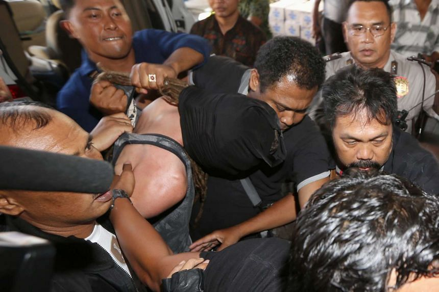 British national David Taylor (wearing a hood) is escorted by police officers after he was arrested over the alleged murder of a police officer in Bali on Aug 19, 2016.