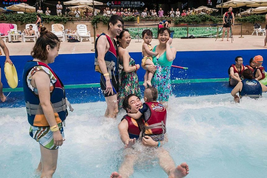 People with life jackets enjoying the waves at the water park in the New Century Global Centre.