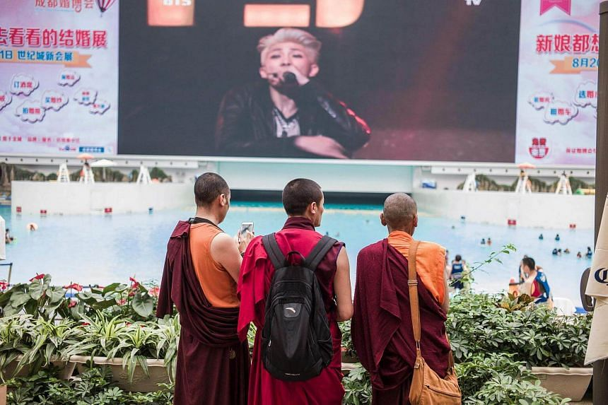 Three monks looking towards the pool at the water park in the New Century Global Centre.