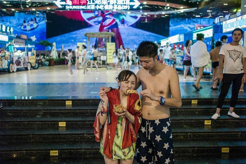 A man feeding snacks to his girlfriend in the water park in the New Century Global Centre.
