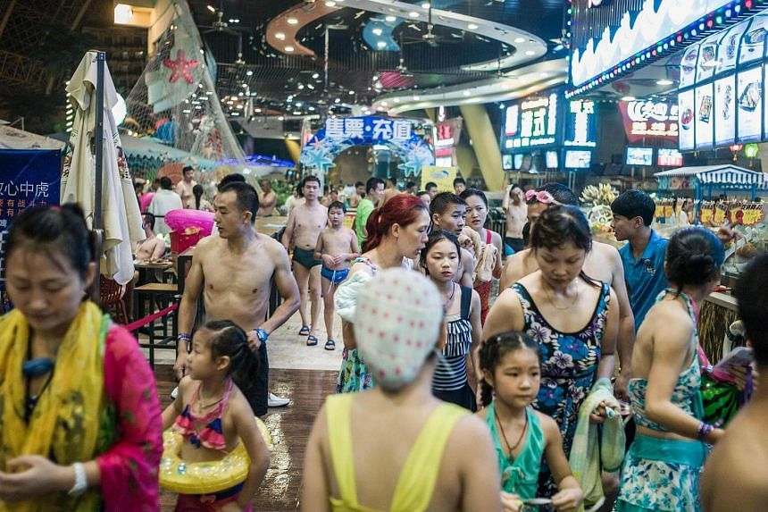 People in swimsuits walk in the water park in the New Century Global Centre.