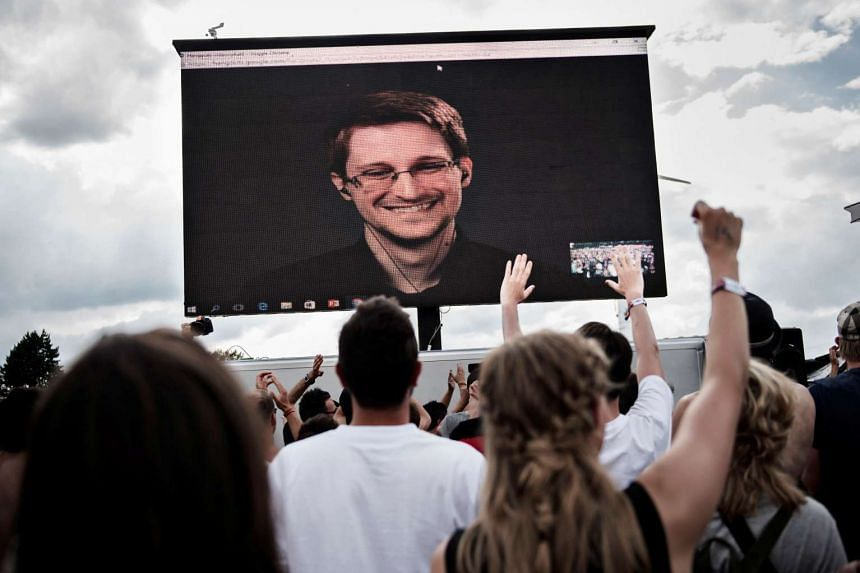 Edward Snowden is seen on a screen as he delivers a speech during the Roskilde Festival in Denmark, June 28 2016.