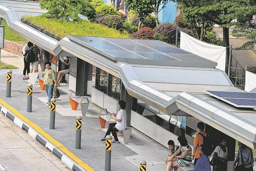 Solar panels are seen on the roof of the bus stop.