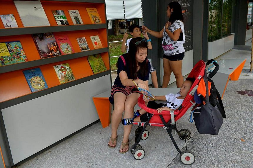 Cathy Xiang 31, reads to her toddler while her other son sits on the swing.
