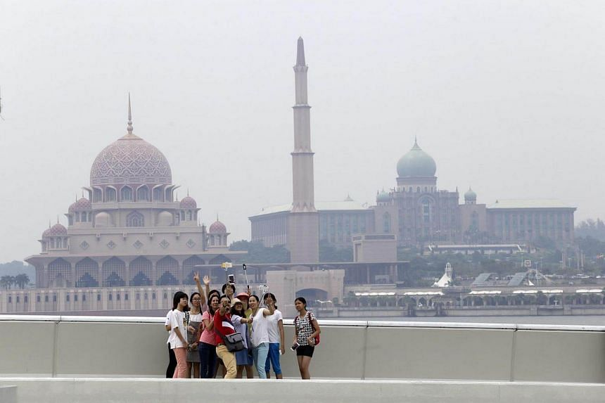 A group of tourists take pictures with the haze-shrouded Putra Mosque (left) and Perdana Putra Building (right) in the background in Putrajaya, Malaysia.