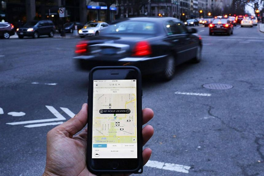 An Uber application being used as cars drive by in Washington, DC on March 25, 2015.