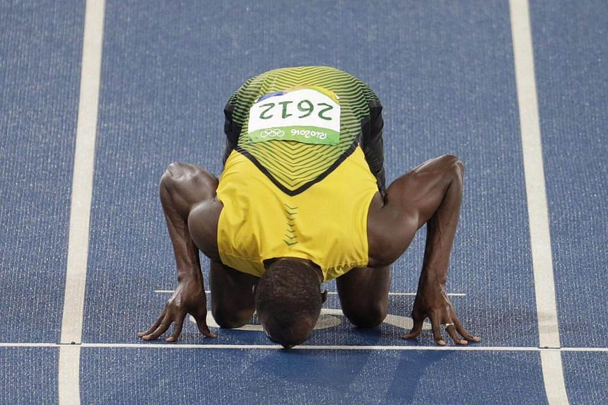 Usain Bolt kisses the track as part of his celebrations after his 200m win.