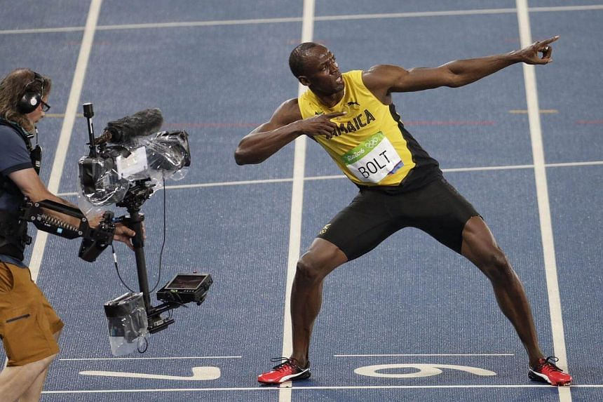 Usain Bolt flashes his signature pose in front of the camera after winning the men's 200m gold.