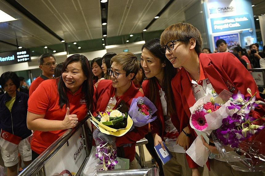 Singapore paddlers (from right) Zhou Yihan, Yu Mengyu and Feng Tianwei posing for photos with their fans upon arrival at Changi Airport yesterday. Despite not winning any Olympic medals for the first time since 2004, the table tennis players were che