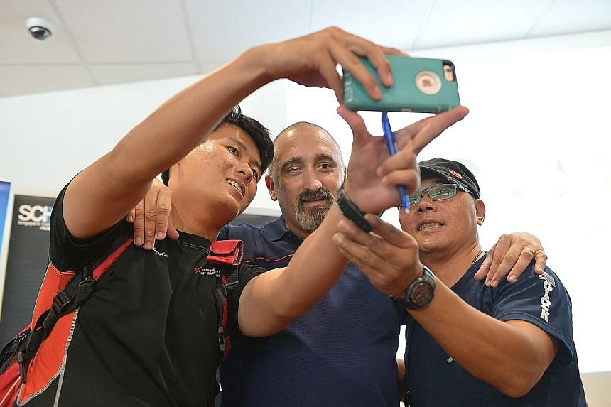 Departing national swimming coach Sergio Lopez poses for photos with participants of a discussion group on the Rio Olympics at the Sports Hub Library yesterday. The Spaniard believes that attitudes are changing among Singaporeans seeking success in s