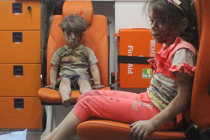 """Omran sitting in an ambulance with his sister on Wednesday after they were rescued following an air strike in a rebel-held neighbourhood in Aleppo. The boy's condition and dazed expression led the US State Department to call him """"the real face"""" of th"""