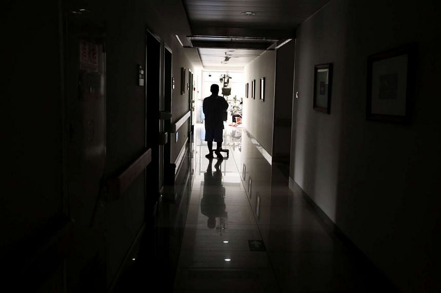 A cancer patient pushes his drip stand as he walks down the hallway of a hospital in Beijing.