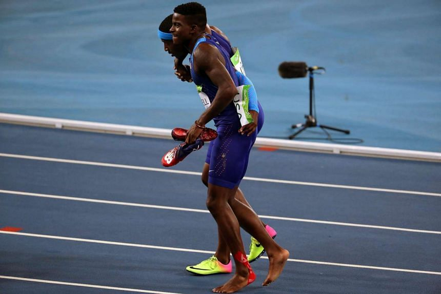 Trayvon Brommell (front) of the US is helped by his teammate Mike Rodgers (back) after falling during the men's 4x100m relay final.