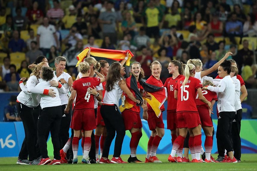 German players and staff celebrate after winning the women's Gold Medal Match between Sweden and Germany.
