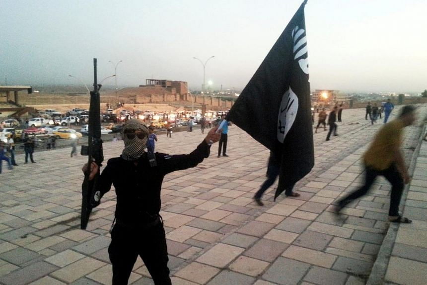 A fighter of the Islamic State of Iraq and the Levant holds an ISIL flag and a weapon on a street in the city of Mosul, on June 23, 2014.