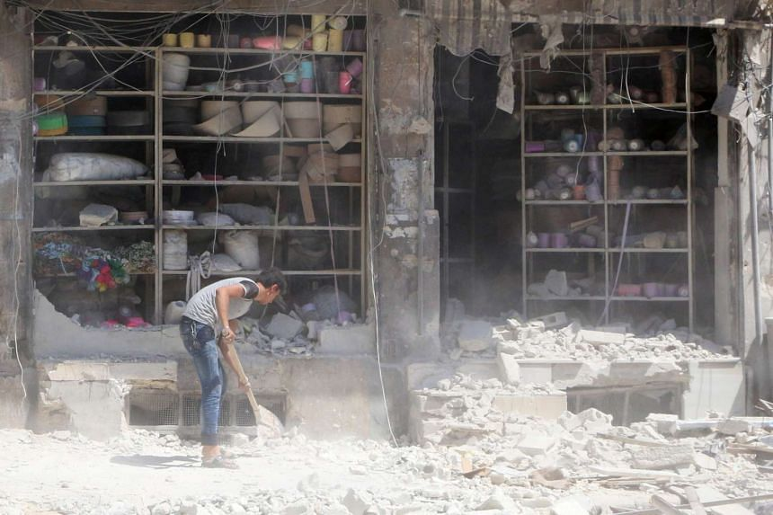 A man removing rubble in front of a damaged shop after an air strike in Aleppo on Aug 18, 2016.