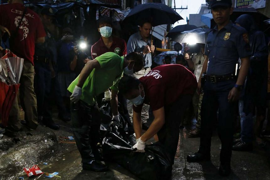 Filipino funeral parlor workers carrying a dead body following a police operation against illegal drugs in Manila on Aug 16, 2016.