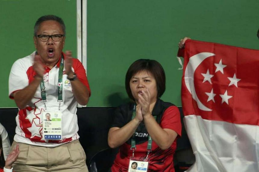 Singapore's Chef de Mission Low Teo Ping cheers as a Singaporean national flag is held up during Singapore's table tennis Bronze medal match against Japan.
