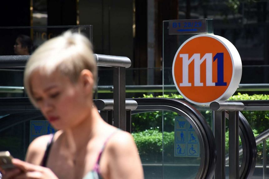 A woman walking past the M1 logo on March 15.