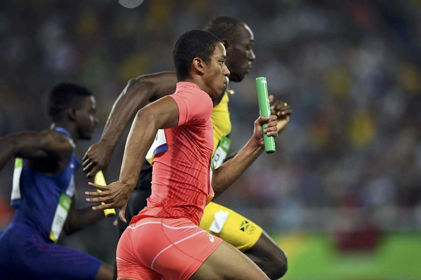 Aska Cambridge (front) of Japan and Usain Bolt (middle) of Jamaica compete in the men's 4x100m relay final.