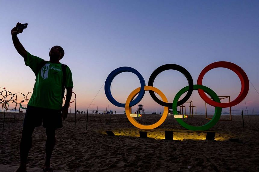 A man takes a selfie in front of the Olympic rings at Copacabana beach in Rio de Janeiro.